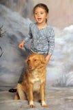 有一条红色狗的小女孩 库存图片