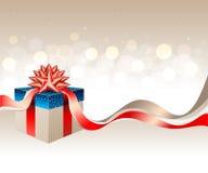 有一条红色金丝带的一个金黄蓝色礼物盒和在轻的发光的bokeh背景的一把弓 免版税库存照片