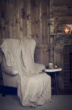 有一条被编织的毯子的扶手椅子 库存照片