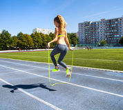 有一条跳绳的少妇在她的有一个体育场的手上作为b 免版税库存图片