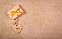 有一条金黄丝带和木心脏的礼物盒 浪漫概念 复制空间 免版税图库摄影
