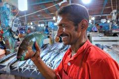 有一条鱼的一个波斯人在他的手上笑 库存图片