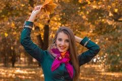 有一条围巾的乐趣俏丽的女孩在他的脖子上提高了手和微笑 免版税库存照片