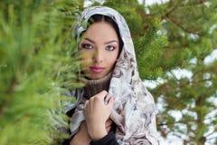 有一条围巾的可爱的少妇在她的头在冷杉木附近的冬天森林,雪落里 免版税图库摄影