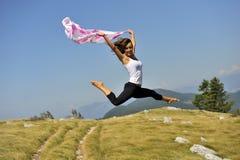 有一条围巾的妇女在有吸引力的跳跃的姿势 免版税库存照片