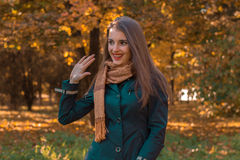有一条围巾的微笑的少妇在立场肩膀在公园和微笑 图库摄影