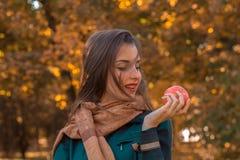 有一条围巾的美丽的女孩在公园在手中站立并且看苹果计算机 免版税库存照片