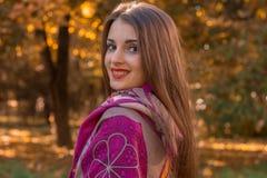 有一条围巾的美丽的女孩在向前仔细地看和微笑的肩膀  库存照片