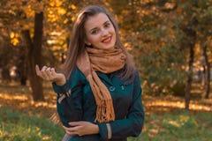 有一条围巾的年轻快乐的女孩在立场肩膀在公园和微笑 库存图片