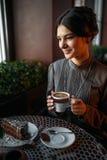 有一杯咖啡的一个女孩在减速火箭的咖啡馆的 免版税库存照片
