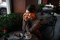 有一杯咖啡的一个女孩在减速火箭的咖啡馆的 免版税图库摄影