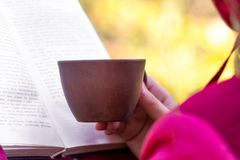 有一杯咖啡的一个女孩读在nature_的一本书 库存照片