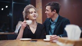 有一杯咖啡的一个好女孩在她的手和快乐地笑她的年轻的男朋友上愉快地谈话和,当在a时 影视素材