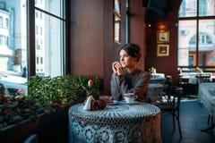 有一杯咖啡的一个年轻美丽的女孩 免版税库存图片