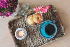 有一杯咖啡的一个盘子、苹果在瓶子,轻链、花和一个蜡烛 库存图片