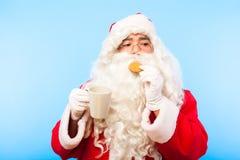 有一杯咖啡的圣诞老人或茶和一个饼干在蓝色ba 库存图片