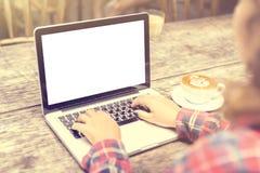 有一杯咖啡的女孩和一台空白的膝上型计算机 图库摄影