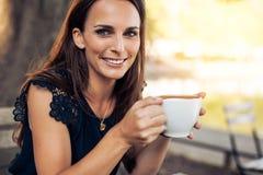 有一杯咖啡的微笑的少妇 库存图片