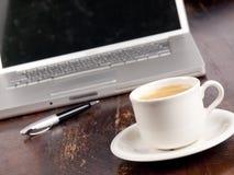 有一杯咖啡的现代膝上型计算机 库存图片
