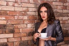有一杯咖啡的美丽的体贴的少妇 有一杯咖啡的性感的女商人 库存照片