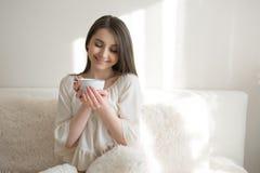 有一杯咖啡的美女在床上的 库存照片