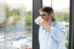 有一杯咖啡的老人在窗口旁边的 免版税库存图片