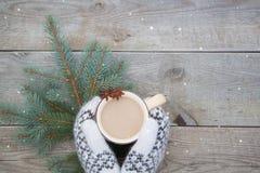 有一杯咖啡的被编织的白色羊毛手套在木背景的cocao 图库摄影