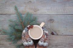 有一杯咖啡的被编织的羊毛手套在木背景的cocao 库存照片