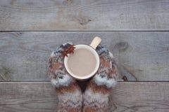 有一杯咖啡的被编织的羊毛手套在木背景的cocao 库存图片