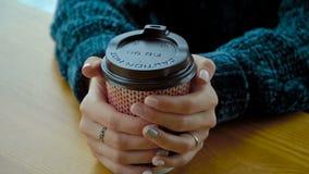 有一杯温暖的热奶咖啡的一纸杯在女孩的手上 股票录像
