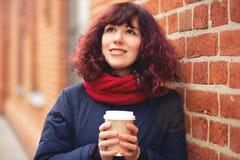 有一杯的女孩咖啡在手中 免版税库存图片