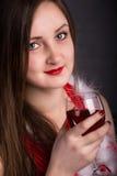 有一杯的女孩在一件红色礼服的酒 库存照片