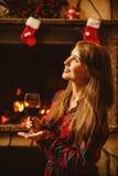 有一杯的妇女由壁炉的酒 年轻有吸引力的wo 免版税库存照片