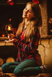 有一杯的妇女由壁炉的酒 年轻有吸引力的wo 库存图片