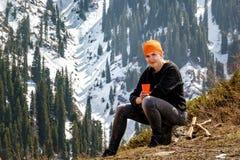 有一杯的妇女茶或咖啡在止步不前在山反对积雪的森林背景在一个晴天 库存照片