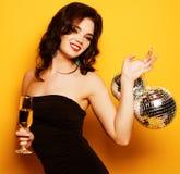 有一杯的性感的妇女在黄色背景的白酒和迪斯科球 免版税库存照片