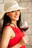 有一杯的端庄的妇女红葡萄酒在地窖里 图库摄影
