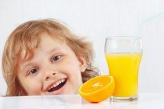 有一杯的美丽的微笑的孩子新鲜的汁液和桔子 免版税库存图片