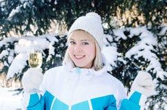 有一杯的美丽的白肤金发的女孩香槟在多雪的冷杉木背景唱歌并且跳舞户外在冬天 免版税库存照片