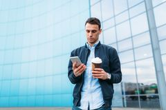 有一杯纸咖啡的一个人,在手中审阅城市,时髦的衣裳的一个英俊的人,有电话的 图库摄影