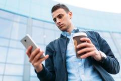 有一杯纸咖啡的一个人,在手中审阅城市,时髦的衣裳的一个英俊的人,有电话的 免版税图库摄影