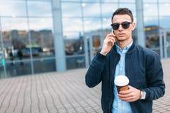 有一杯纸咖啡的一个人,审阅城市、一个英俊的人时髦的衣裳的和太阳镜,打电话 库存照片