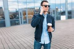 有一杯纸咖啡的一个人,审阅城市、一个英俊的人时髦的衣裳的和太阳镜,打电话 免版税图库摄影
