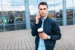 有一杯纸咖啡的一个人,审阅城市,时髦的衣裳的一个英俊的人,在电话 免版税库存图片