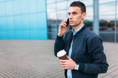 有一杯纸咖啡的一个人,审阅城市,时髦的衣裳的一个英俊的人,在电话 图库摄影