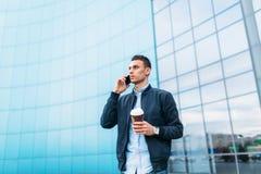 有一杯纸咖啡的一个人,审阅城市,时髦的衣裳的一个英俊的人,在电话 免版税图库摄影