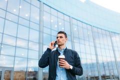 有一杯纸咖啡的一个人,审阅城市,时髦的衣裳的一个英俊的人,在电话 免版税库存照片