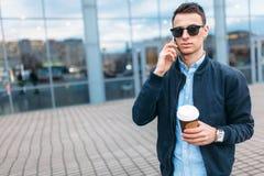 有一杯纸咖啡的一个人,审阅城市,时髦的衣裳的一个英俊的人,在电话 库存图片