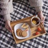 有一杯茶和一块板材的盘子用姜饼干和一个苹果在一条方格的床罩 库存照片