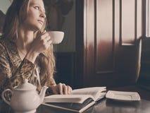 有一杯茶的一个年轻美丽的女孩 免版税库存图片